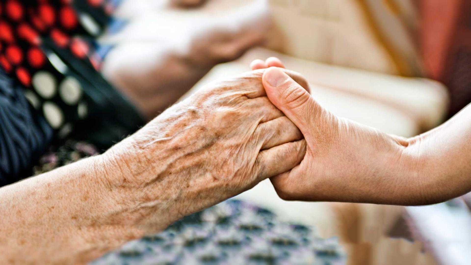 Elderly hand being held by younger hand
