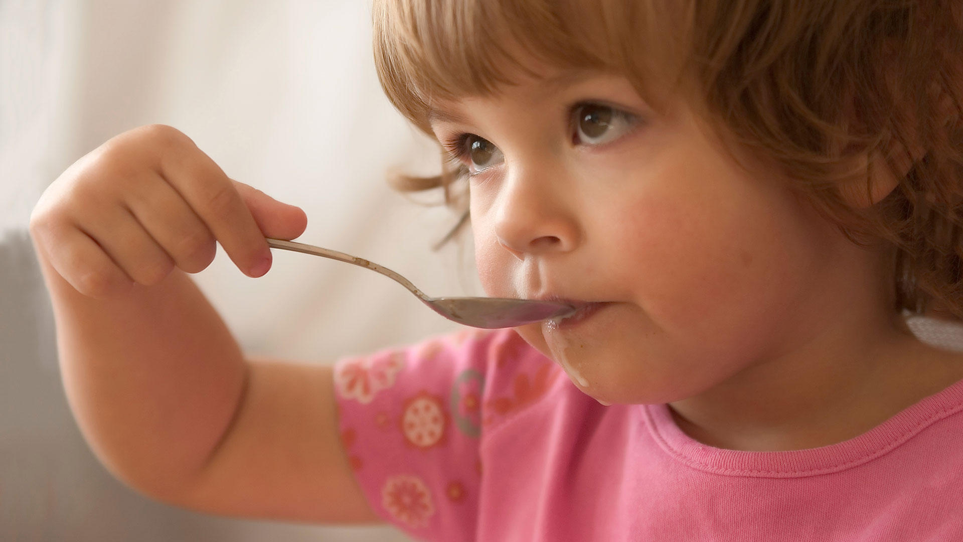 Child eating cereal from a spoon
