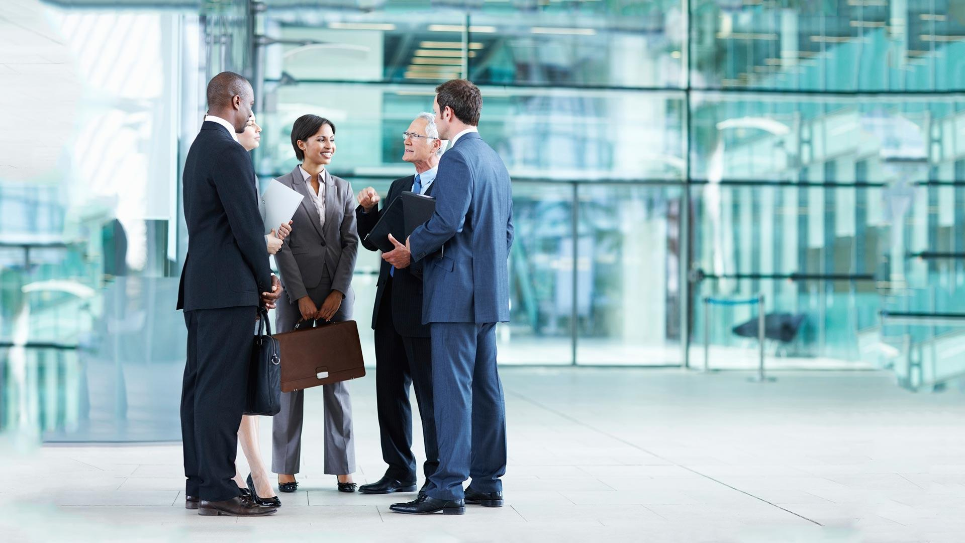 Businessmen and woman standing, discussing business