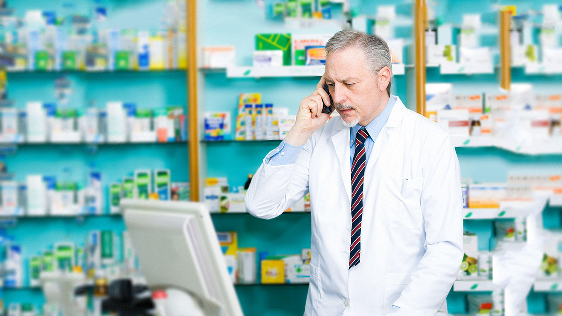 Pharmacist on the phone in front of a computer