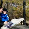Mother and child reading a park sign